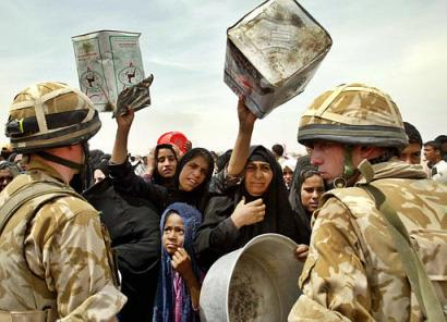 Iraqi women reach out with empty water containers as British soldiers arrive to supply the outskirts of Iraqi's southern city of Basra with drinking water, Friday, April 4, 2003. (AP Photo/Anja Niedringhaus)